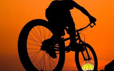Mann auf Mountainbike im Abendrot