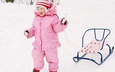 Kind in Rosa steht mit Schlitten im Schnee