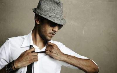 Mann in Hemd und Krawatte mit Hut und Sonnenbrille