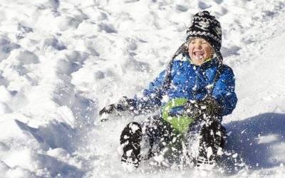 Kind rodelt und Schnee wirbelt auf