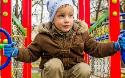 Kind auf Spielplatz an Klettergerüst