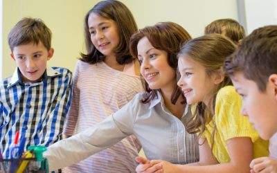 Schüler und Lehrer gemeinsam vor einem Computer