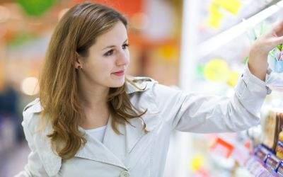 Frau kauft gutgelaunt in Supermarkt ein
