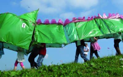 Kinder spielen mit einem grünen Drachen