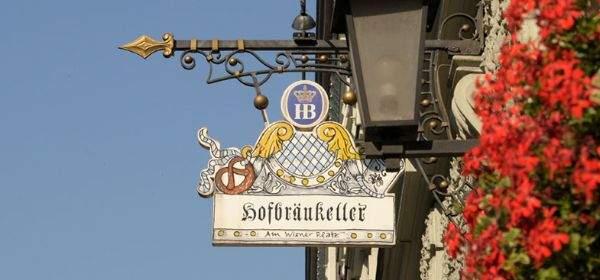 Schild des Hofbräukellers vor blauem Himmel