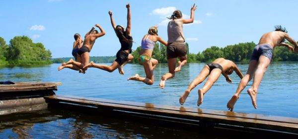 Jugendliche springen in Badesee
