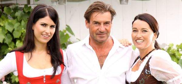 Mann in Lederhosen mit zwei Frauen in Dirndl