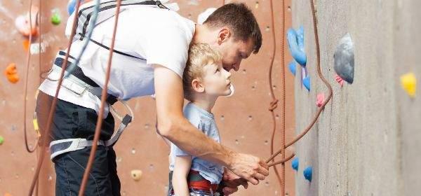 Vater hilft Sohn mit Klettergurten