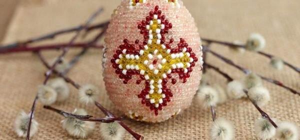Ein mit einem Kreuz verziertes Osterei liegt neben einem Palmzweig.
