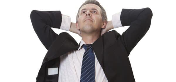 Mann im Anzug verschränkt die Arme hinter dem Kopf