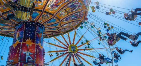 Frühlingsfest: Karussell mit Riesenrad im Hintergrund